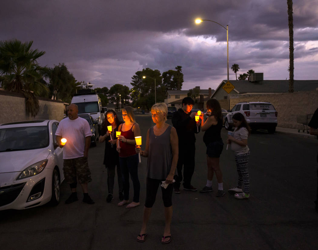 People hold candles during a vigil in memory of Jennifer Ratay outside of the home where she wa ...