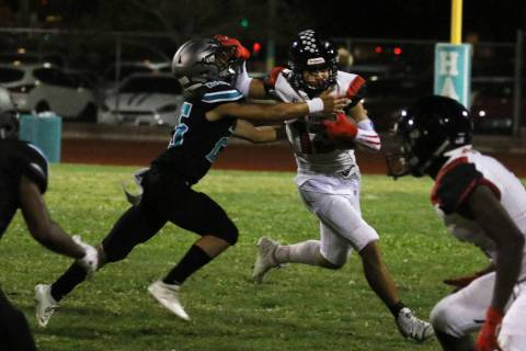 Las Vegas High's wide receiver Dalten Silet (13) avoids a tackle from Silverado High's Jeremy A ...