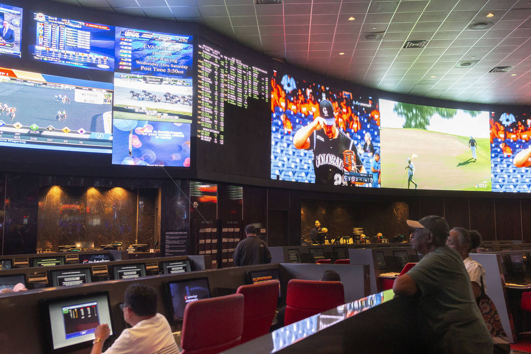 Bettors watch live sports at the CG Technology sportsbook at the Palms in Las Vegas, July 25, 2 ...