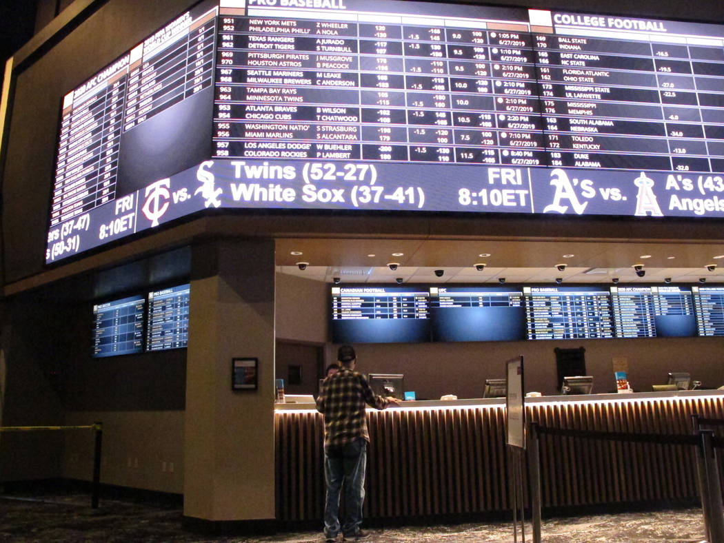 A customer ponders the odds at the new sportsbook at Bally's casino in Atlantic City, N.J., Jun ...
