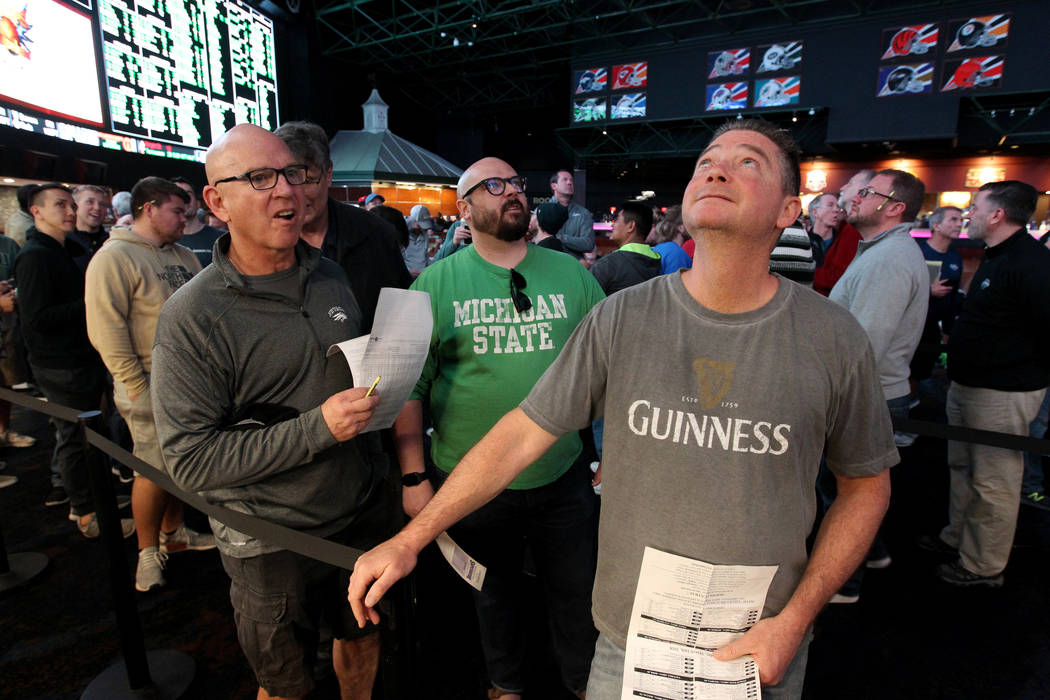 Steve Buckley of Boston, right, lines up to bet on basketball games during the NCAA Tournament ...