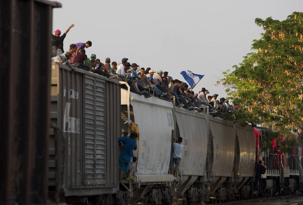 FILE - In this April 23, 2019 file photo, Central American migrants ride atop a freight train d ...