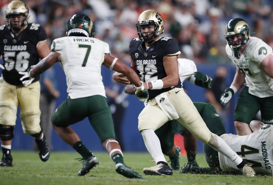 Colorado State safety Jamal Hicks, left, comes in to tackle Colorado quarterback Steven Montez, ...