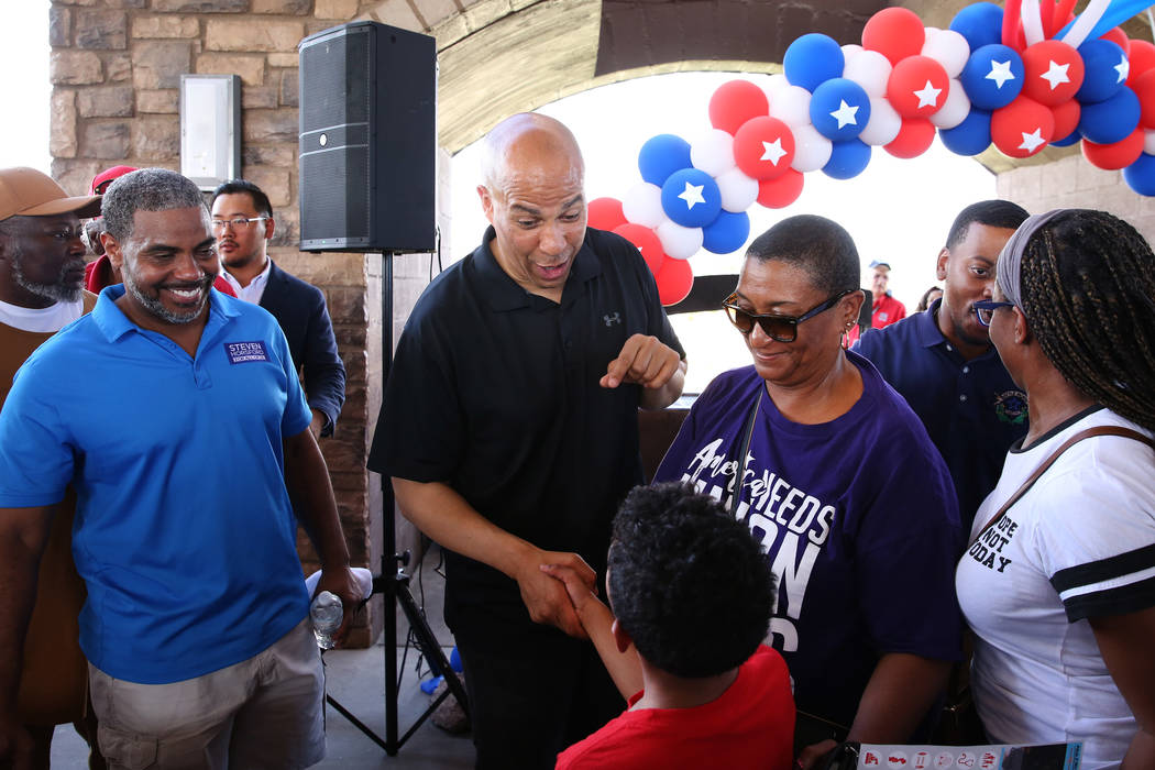 Democratic presidential candidate Sen. Cory Booker, D-N.J., second left, shakes hands with Will ...