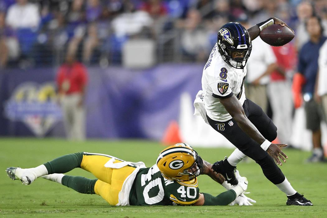 Baltimore Ravens quarterback Lamar Jackson, right, avoids a hit fromGreen Bay Packers linebacke ...