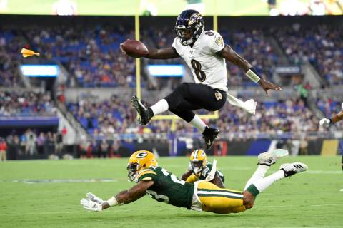 Baltimore Ravens quarterback Lamar Jackson (8) leaps over Green Bay Packers cornerback Jaire Al ...