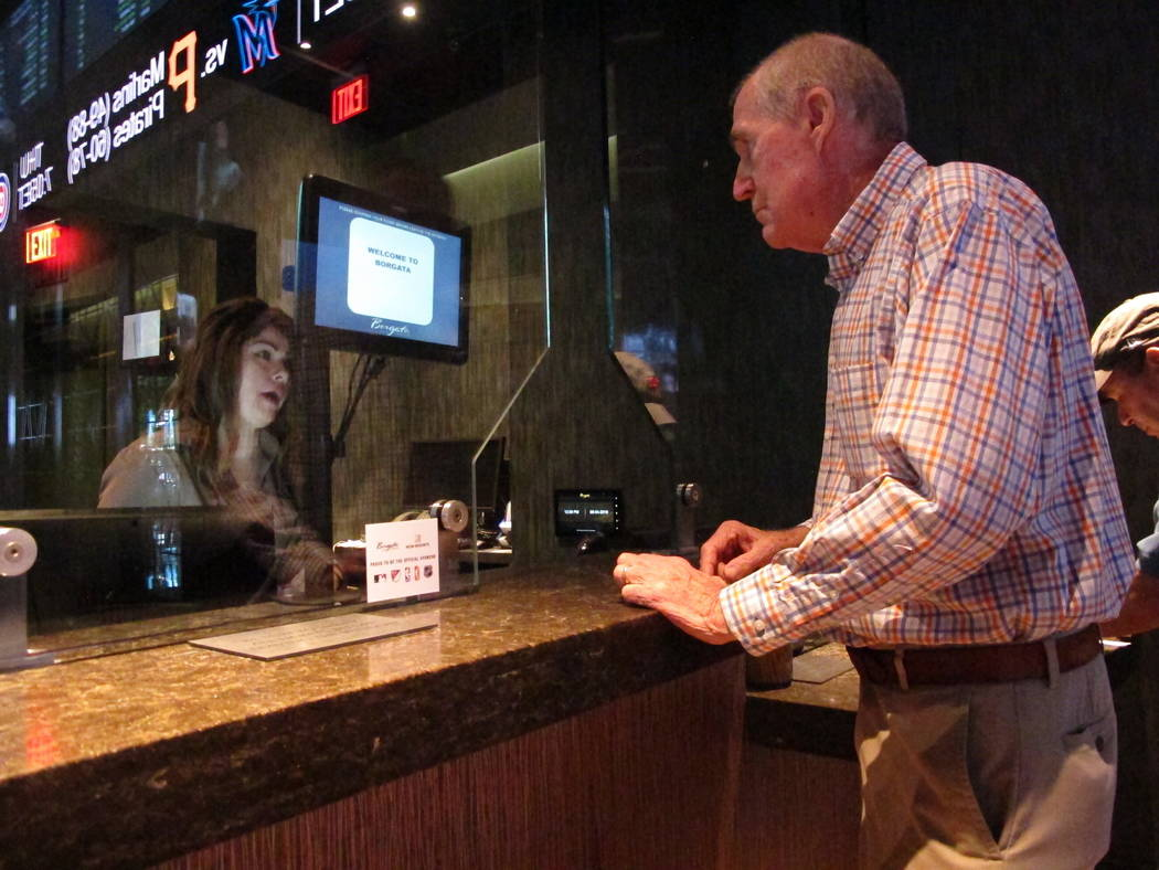 This Sept. 4, 2019 photo shows a customer checking the odds at the sports book at the Borgata c ...