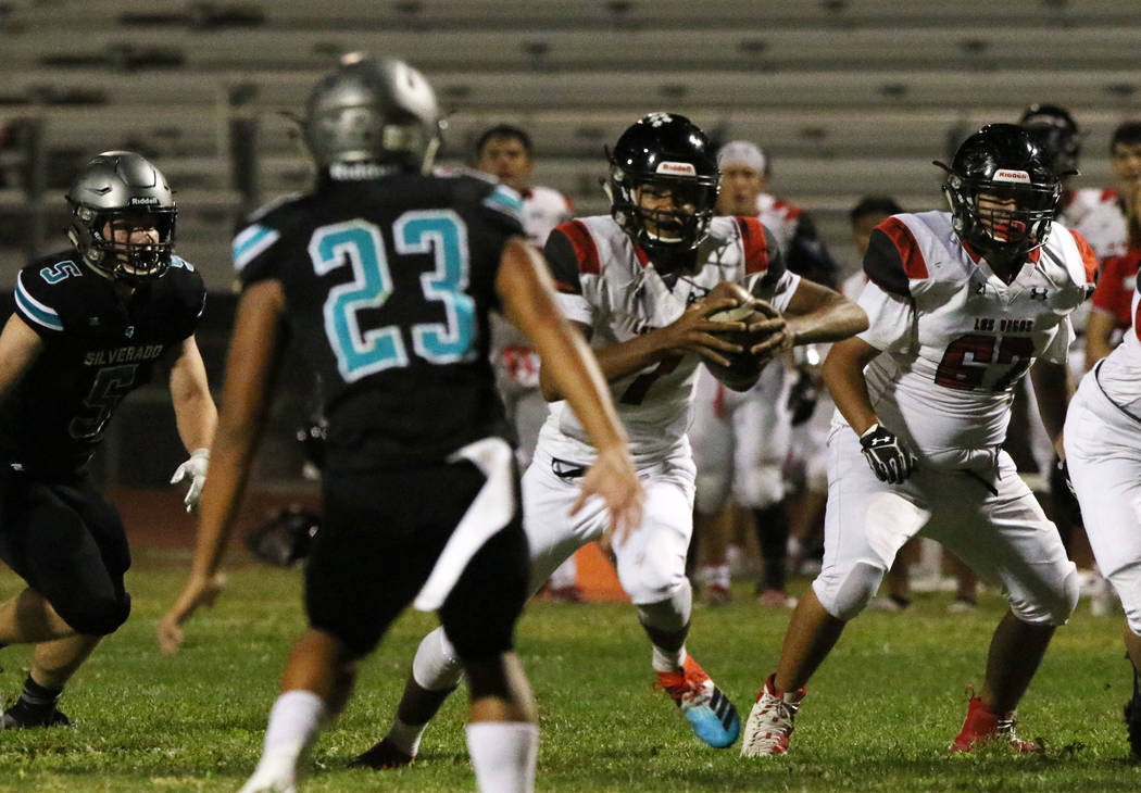 Las Vegas High's quarterback Ja'shawn Scroggins, second right, runs with the ball during the fi ...