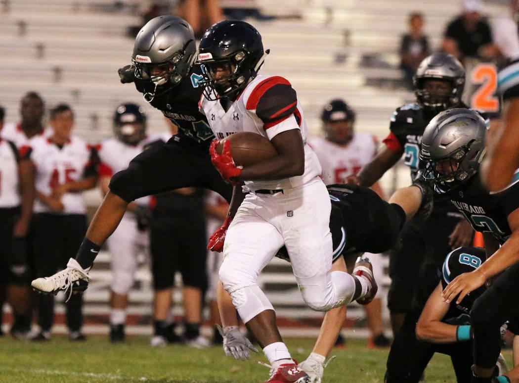 Las Vegas High's Jay Curtis (5) scrambles away from Silverado High's quarterback Ryan Kelly (8) ...