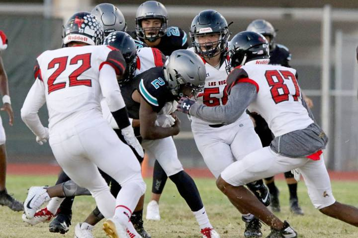 Silverado High's running back Aginae Cunningham (2) is tackled by Las Vegas High defense during ...