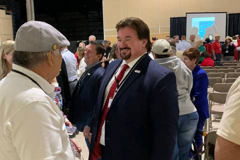 Nevada state GOP chairman Michael McDonald speaks to party delegates standing on line to vote f ...