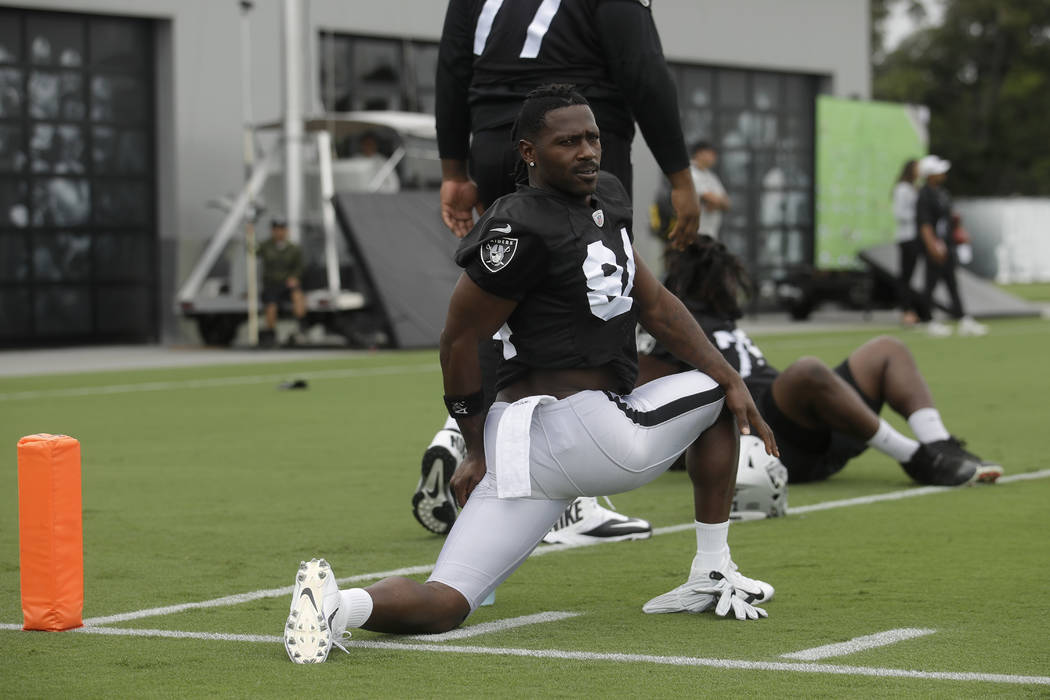 Oakland Raiders' Antonio Brown stretches during NFL football practice in Alameda, Calif., Tuesd ...