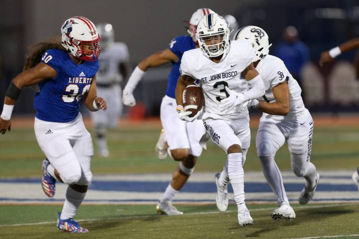 St. John Bosco's Jode McDuffie (3) runs the ball for a touchdown under pressure from Liberty's ...