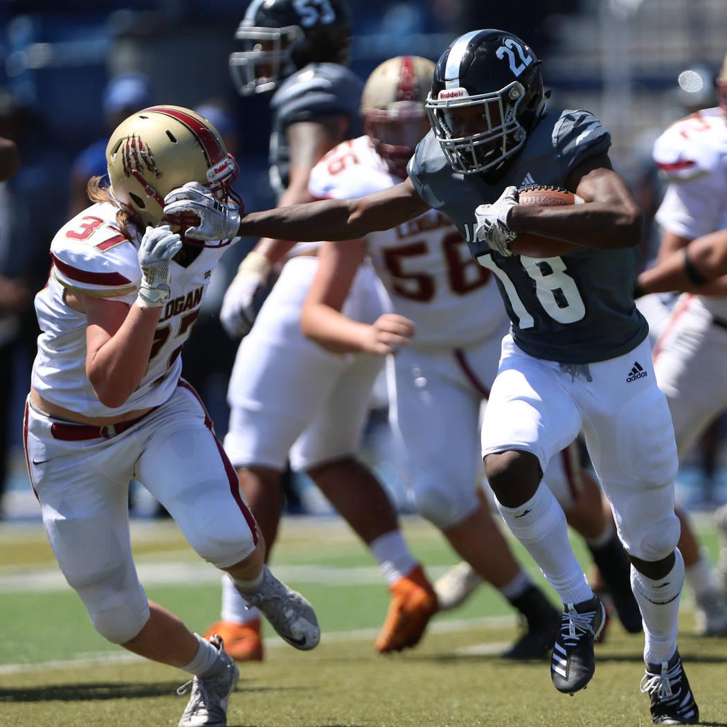 Desert Pines' Ja' Juan Pollard (18) runs the for a touchdown against Logan's Andrew Thompson (3 ...