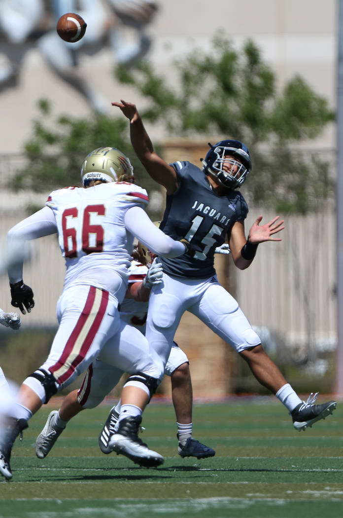 Desert Pines' Rjay Tagatases (15) throws the ball under pressure from Logan's Tennyson Hadfield ...
