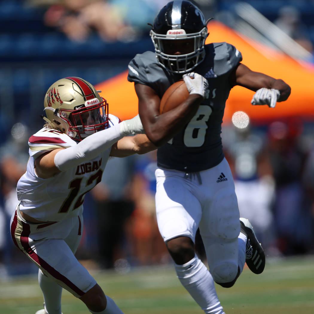 Desert Pines' William Paden iii (8) runs the for a touchdown against Logan's Tyson Sauer (12) d ...