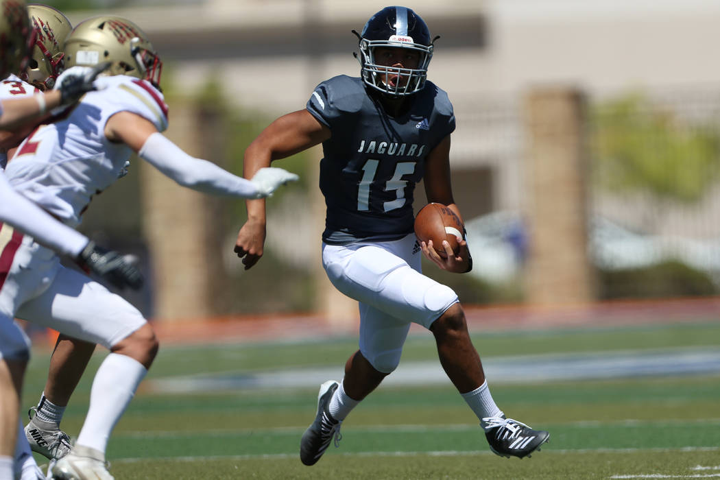 Desert Pines' Rjay Tagatases (15) runs the ball against Logan during the first quarter of the P ...