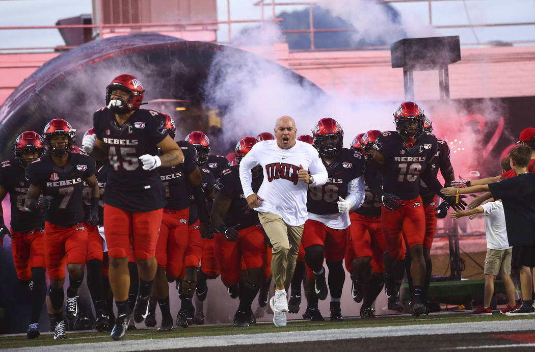 UNLV Rebels head coach Tony Sanchez leads his team onto the field before playing Arkansas Stat ...