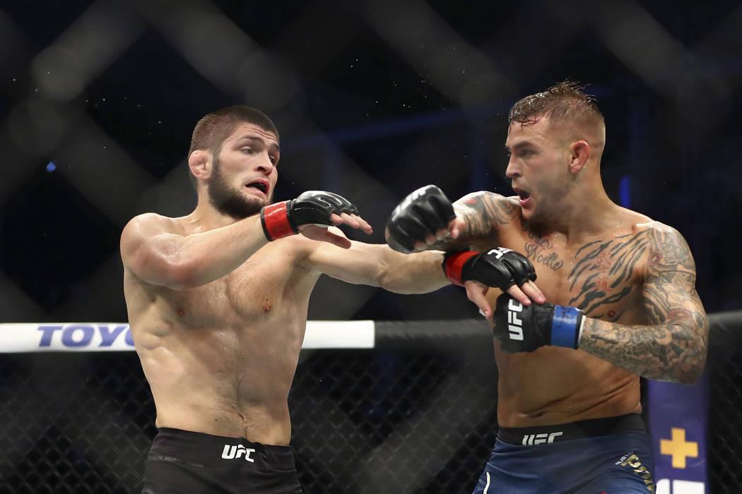 Russian UFC fighter Khabib Nurmagomedov, left, fights with UFC fighter Dustin Poirier, of Lafay ...