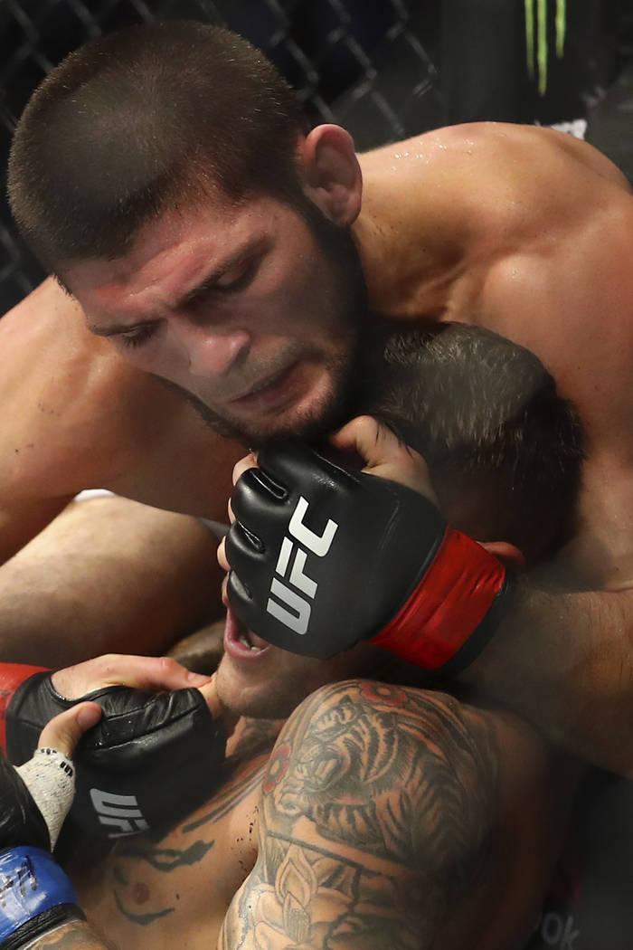 Russian UFC fighter Khabib Nurmagomedov, top, fights with UFC fighter Dustin Poirier, of Lafaye ...