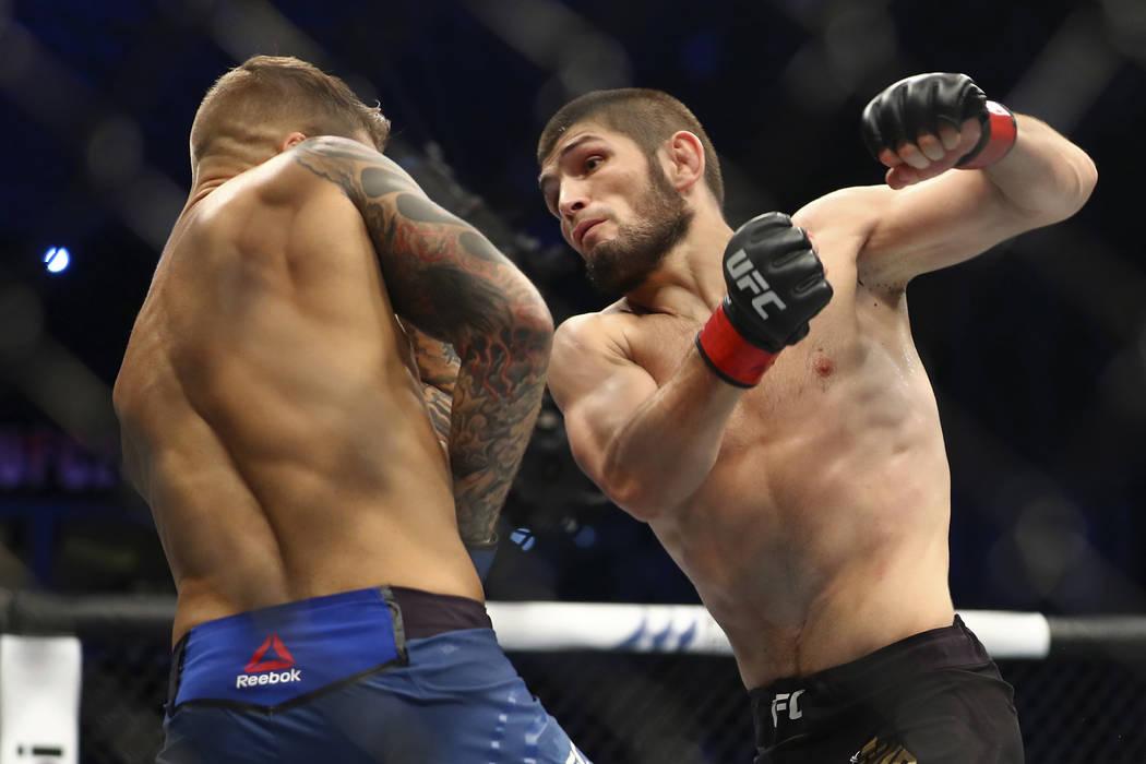 Russian UFC fighter Khabib Nurmagomedov, right, fights with UFC fighter Dustin Poirier, of Lafa ...