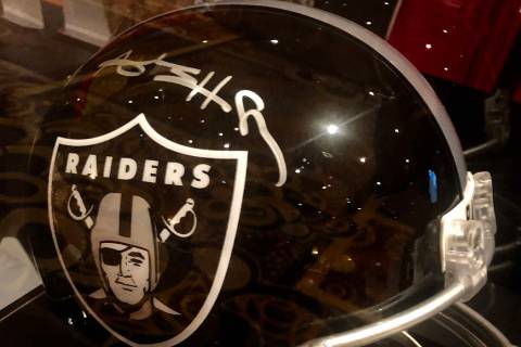 A modified, all-black helmet with a Raiders' logo and signed by Antonio Brown is shown at the a ...