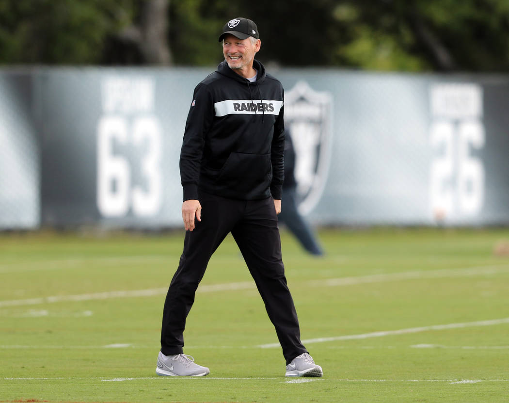 Oakland Raiders general manager Mike Mayock smiles on the field during an offseason training se ...