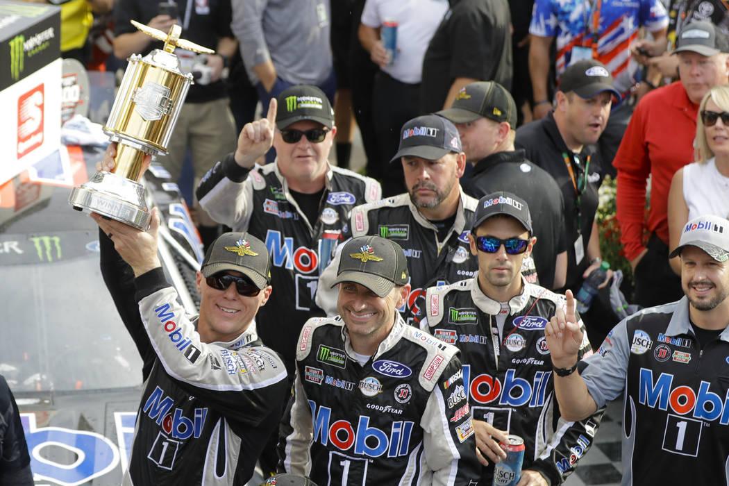 Kevin Harvick, left, celebrates after winning the NASCAR Brickyard 400 auto race at Indianapoli ...
