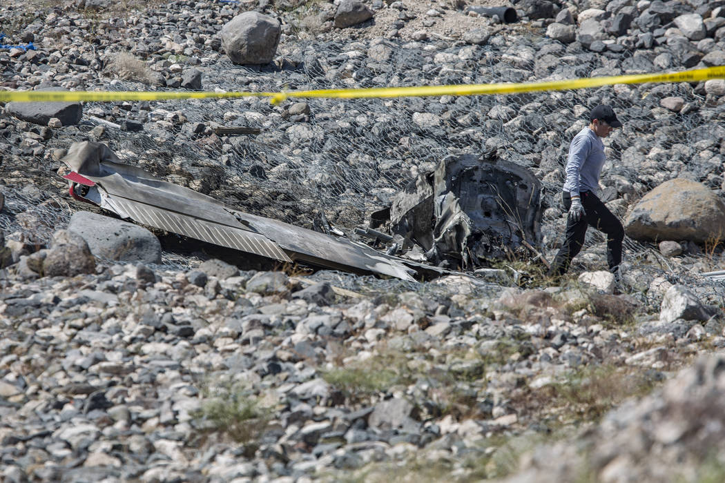 A Federal Aviation Administration employee investigates the scene of an airplane crash from Sat ...