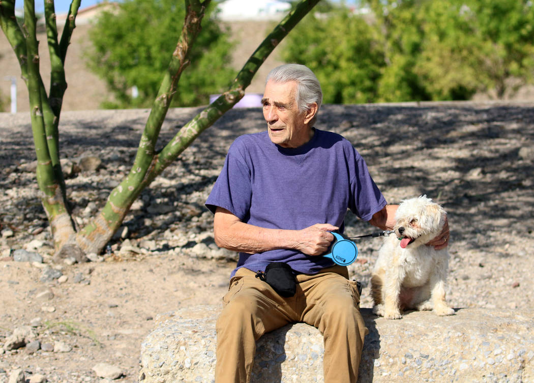 Don Bakkila of Henderson and his dog, Dilly, take a break from their morning walk at Cornerston ...