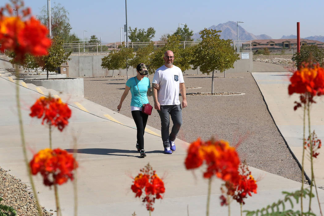 Adam Gnesia and his wife, who declined to give her name, both of Henderson, walk during a sunny ...