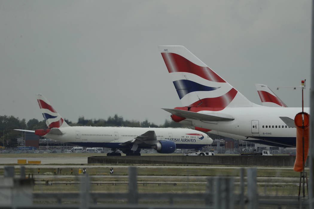 A British Airways plane, at left, is towed past other planes sitting parked at Heathrow Airport ...