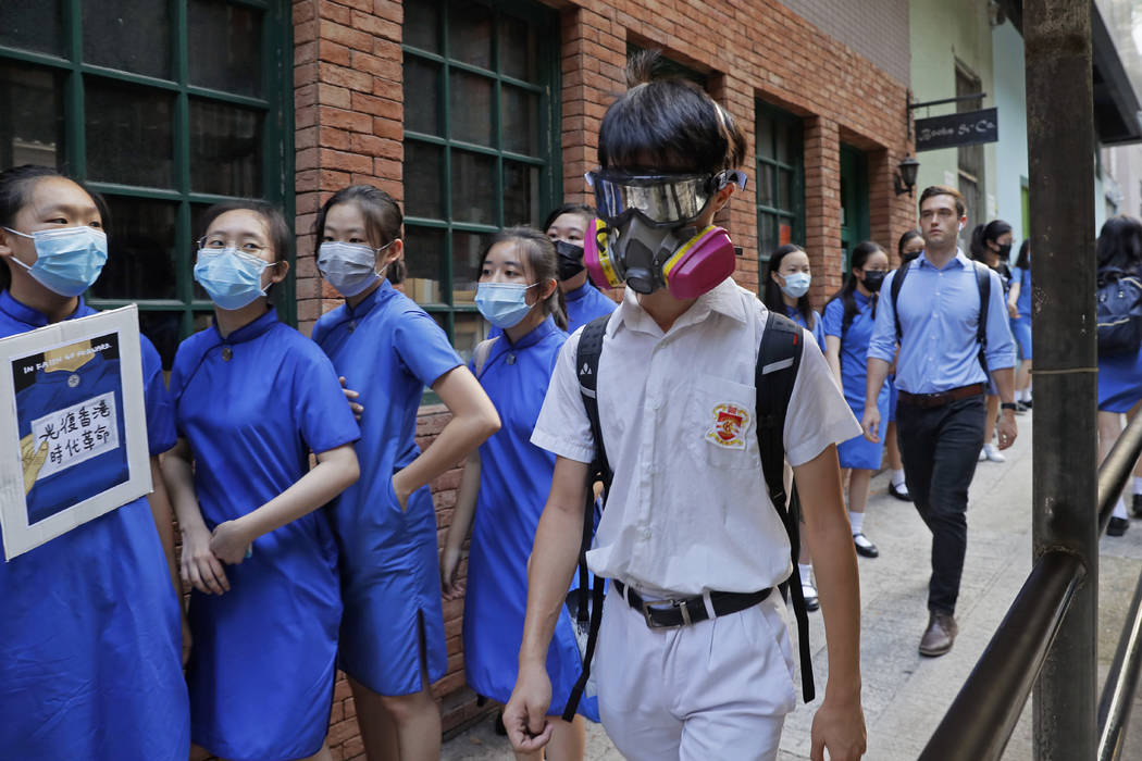 Students wearing mask hold hands to surround the St. Stephen's Girls' College in Hong Kong, Mon ...