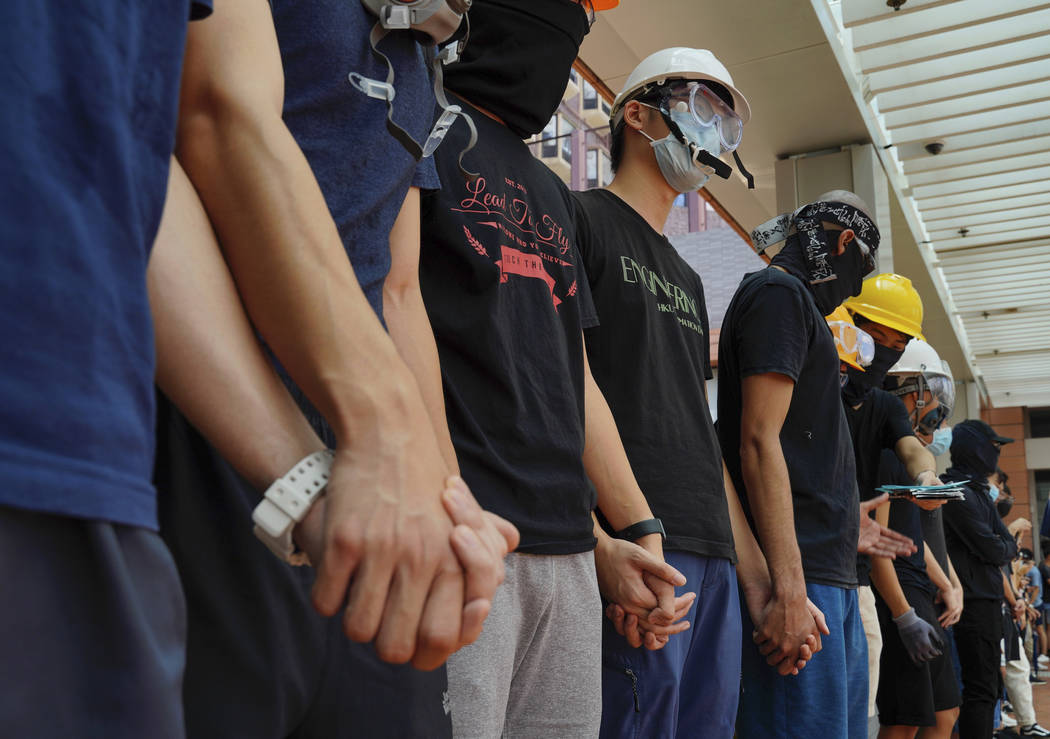 Students from Hong Kong University chains their hands outside schools in Hong Kong, Monday, Sep ...