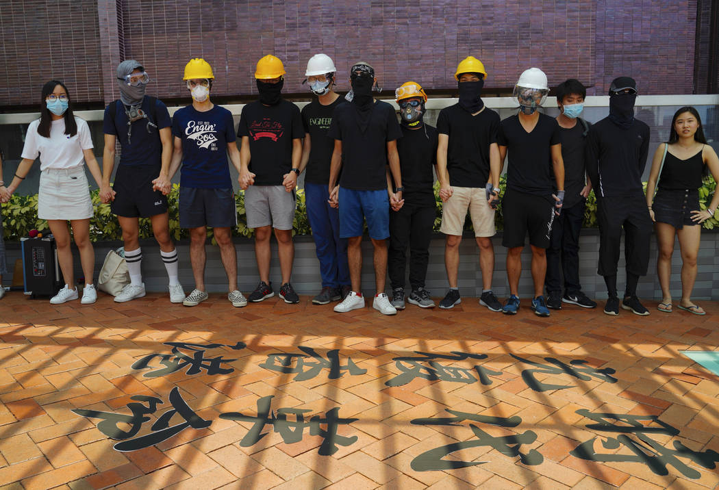 Students from Hong Kong University join their hands and shout slogans near Chinese calligraphy ...