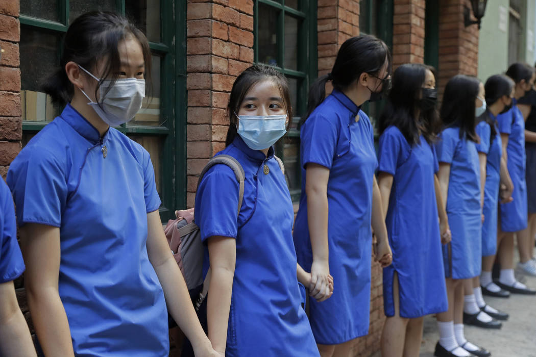 Students wearing mask hold hands to surround St. Stephen's Girls' College in Hong Kong, Monday, ...