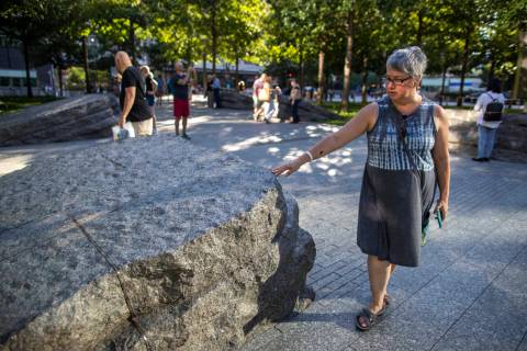 In this Thursday, Aug. 29, 2019, photo a visitor touches one of the granite slabs at the 9/11 M ...