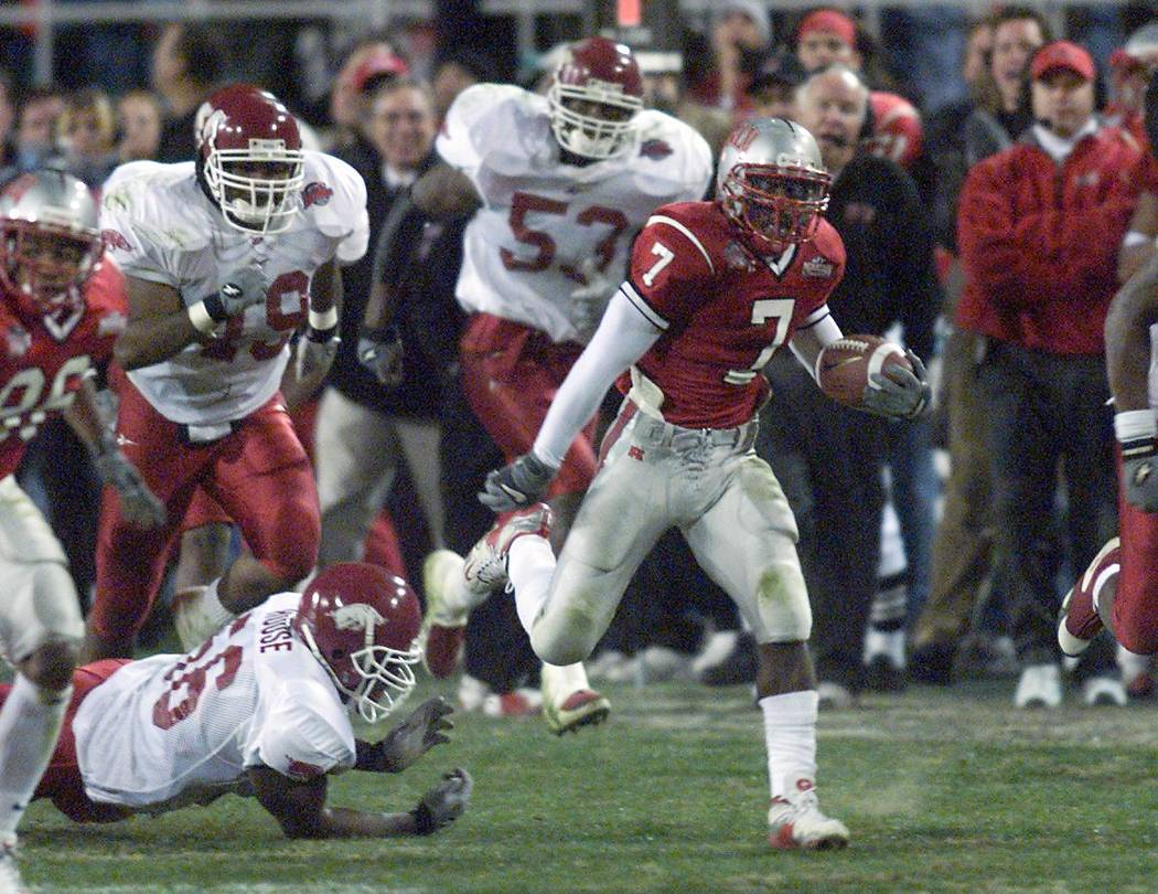 UNLV running back Jeremi Rudolph breaks a tackle by Arkansas defensive end Raymond House for a ...
