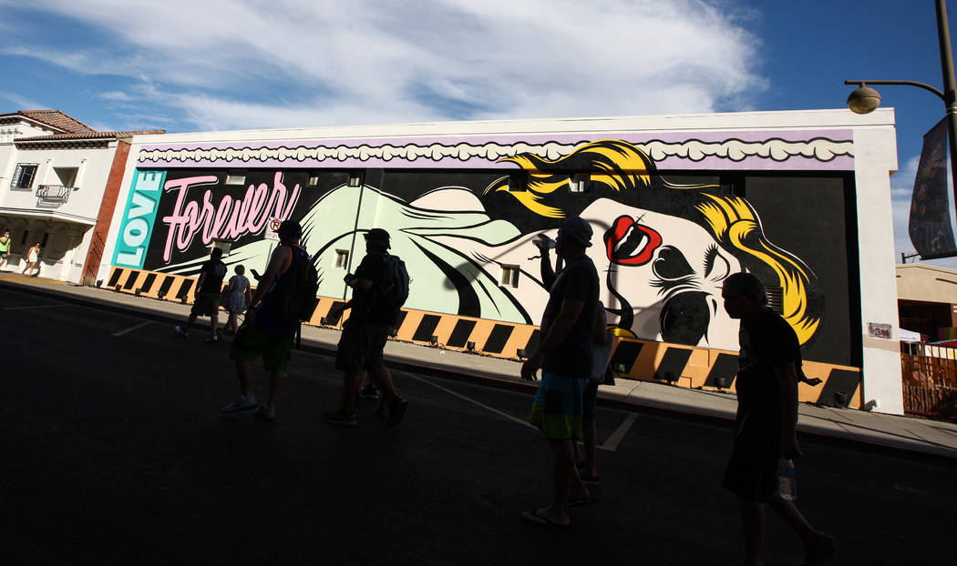 Attendees pass by a mural during the Life is Beautiful festival in downtown Las Vegas on Saturd ...