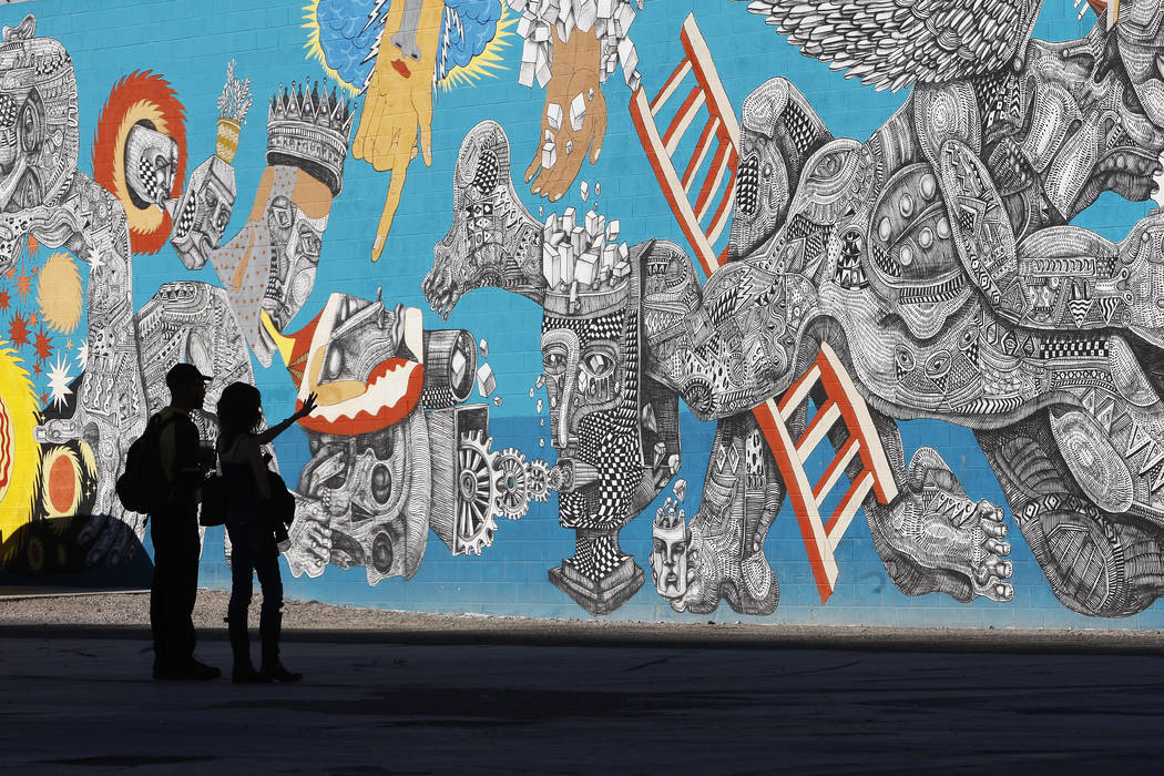 Pedestrians look at a mural that was created for last year's Life is Beautiful festival in down ...