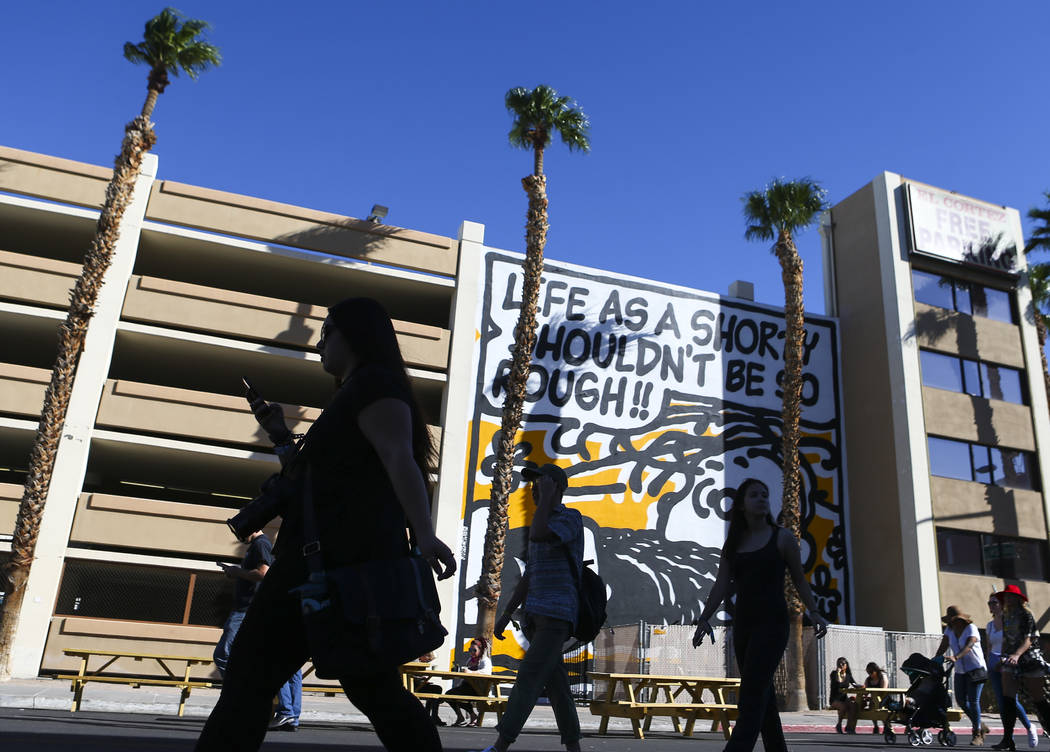Attendees pass by a mural during the Life is Beautiful music and arts festival in downtown Las ...