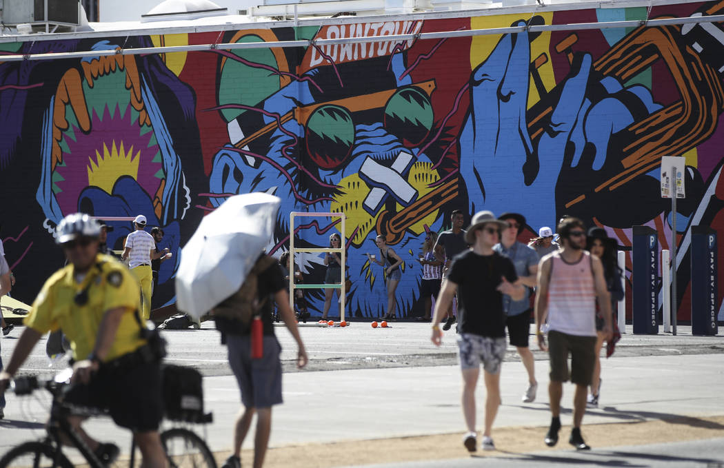 Attendees pass by a new mural during the first day of the Life is Beautiful festival in downtow ...