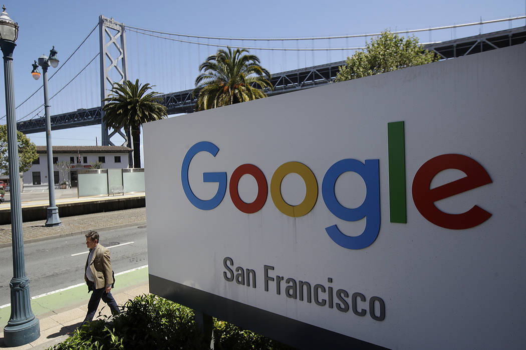 FILE - In this May 1, 2019, file photo a man walks past a Google sign outside with a span of th ...