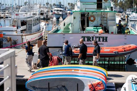Authorities walk outside the Truth, a Truth Aquatics-owned dive boat, docked in the Santa Barba ...