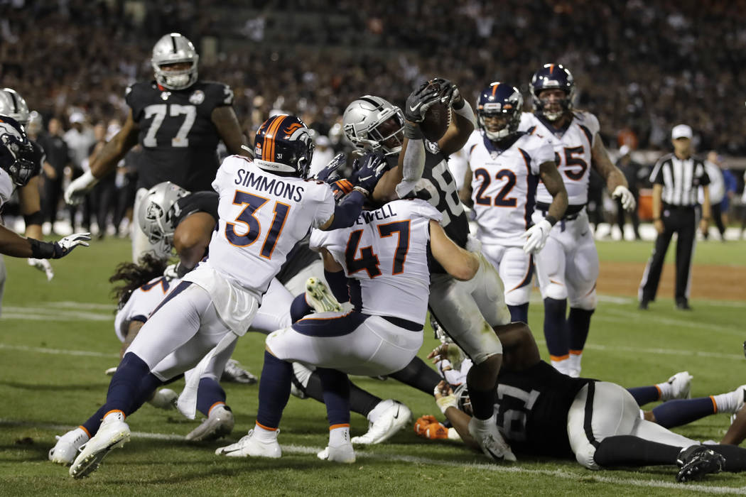 Oakland Raiders running back Josh Jacobs (28) scores a touchdown as Denver Broncos free safety ...
