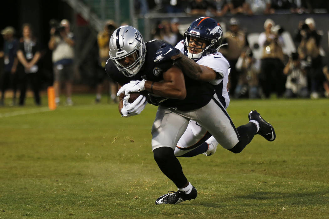Oakland Raiders wide receiver Tyrell Williams scores a touchdown as Denver Broncos free safety ...