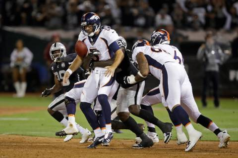 Denver Broncos quarterback Joe Flacco is sacked by Oakland Raiders defensive end Benson Mayowa ...