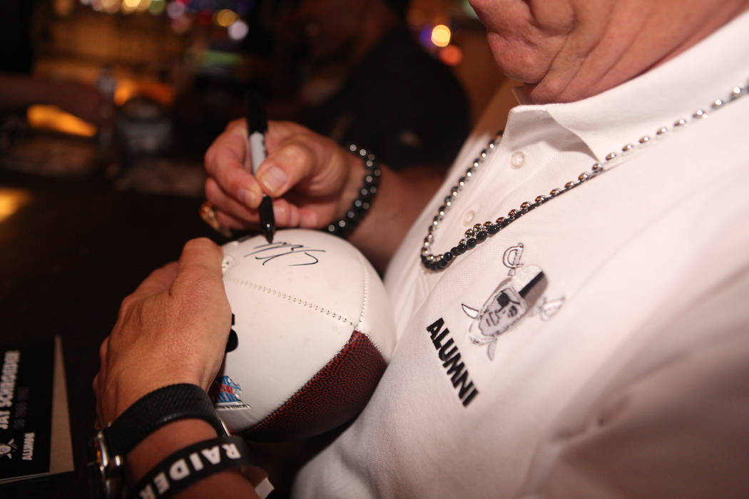 Former Oakland Raider Jay Schroeder signs a football for a fan during a autograph fan signing a ...