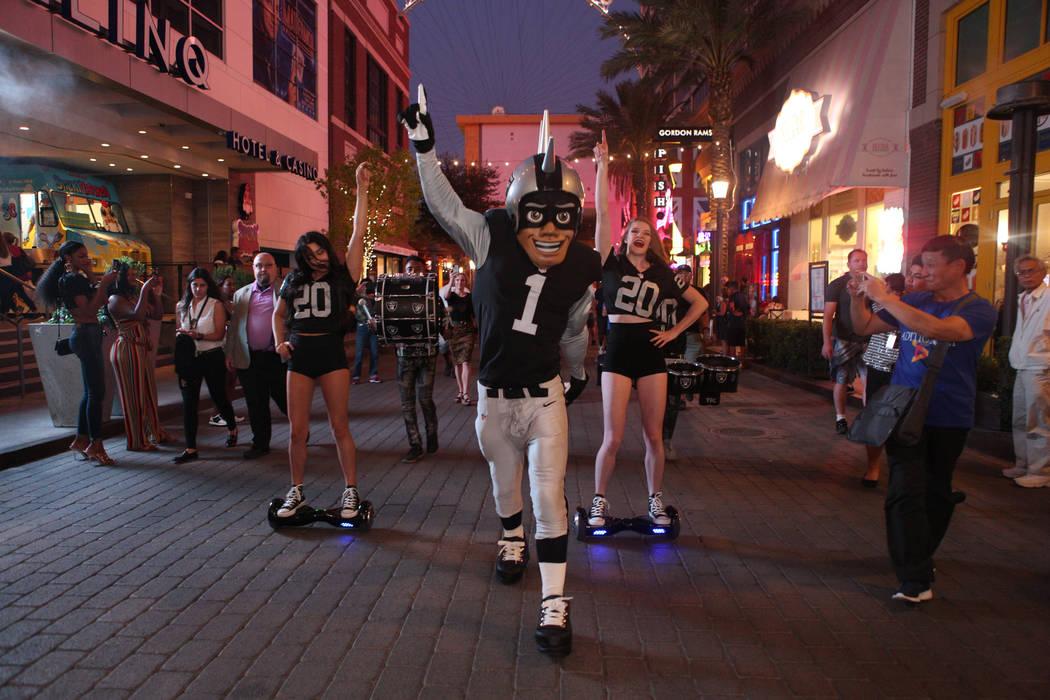 The Oakland Raiders mascot celebrates with Diana Tatevossian, left, and Kayla Kalisz, right, of ...
