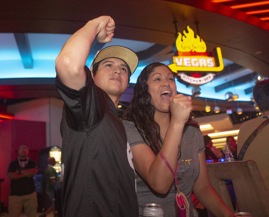 Oakland Raiders fan Jason Estrada, left, cheers with his girlfriend Demi Hart, right, during th ...
